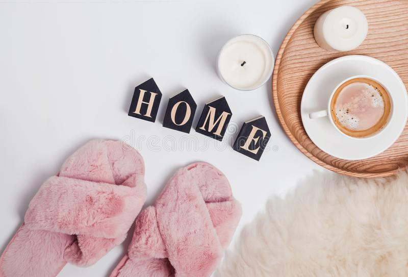 Pink fluffy feminine slippers, coffee and wooden letters arranged in a word Home stock photos