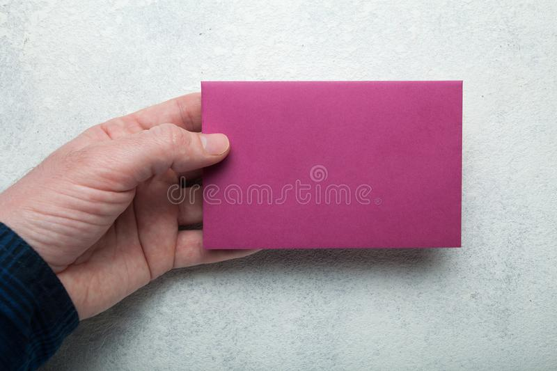 Pink A6 format in the hand. An empty layout. Mock up stock photo