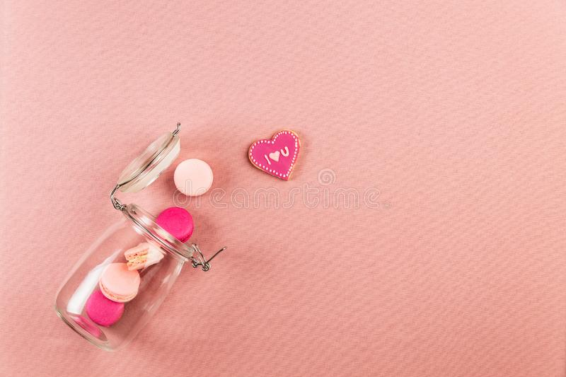 Pink and magenta french macarons or macaroons, and I love you cookie falling out of a glass jar. Pink background and copy space royalty free stock photography