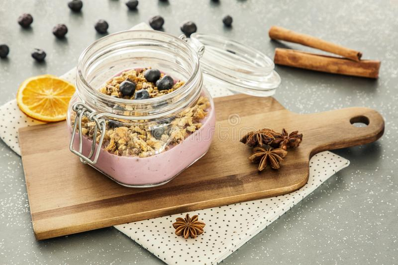 Pink, fruit yogurt with granola and blueberries in a jar on a wooden cutting board and cinnamon spice on a gray kitchen counter royalty free stock photo