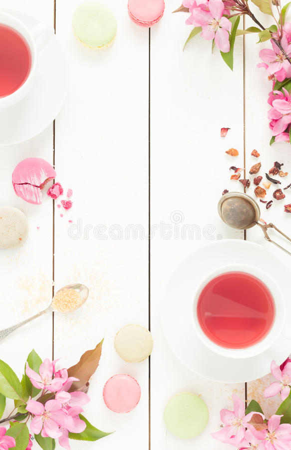 Pink fruity tea and pastel french macarons cakes on white. Pink fruity tea and pastel french macarons cakes on rustic white wooden background. Dessert in a stock photo