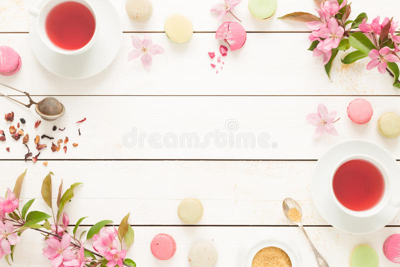 Pink fruity tea and pastel french macarons cakes on white. Pink fruity tea and pastel french macarons cakes on rustic white wooden background. Dessert in a royalty free stock photo