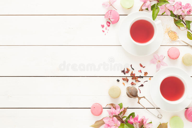 Pink fruity tea and pastel french macarons cakes on white. Pink fruity tea and pastel french macarons cakes on rustic white wooden background. Dessert in a stock images