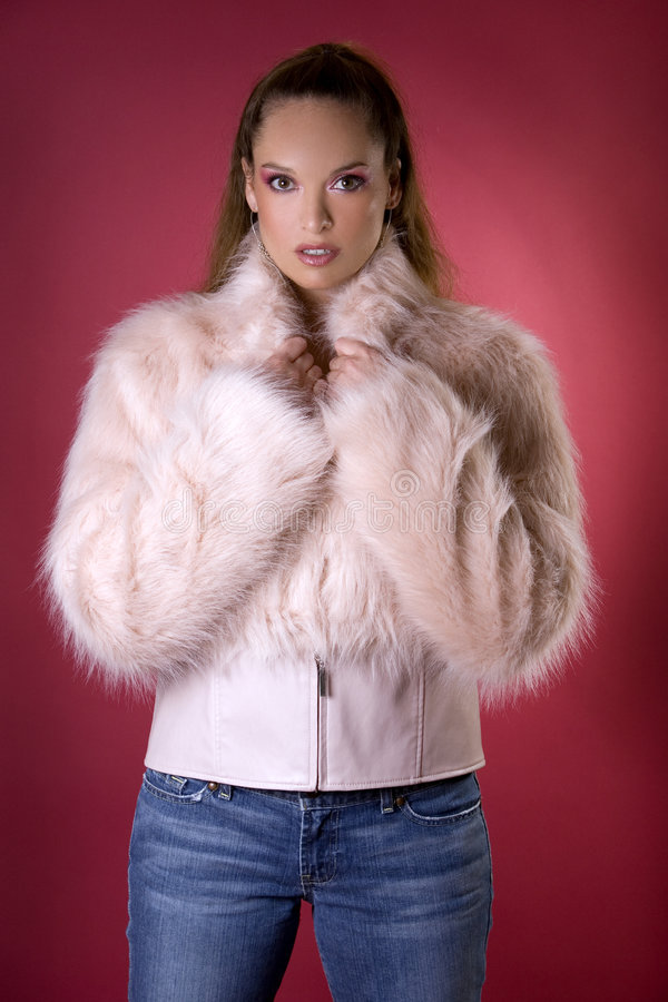Pink fur coat. Pretty model wearing pink fur coat and blue jeans stock photo