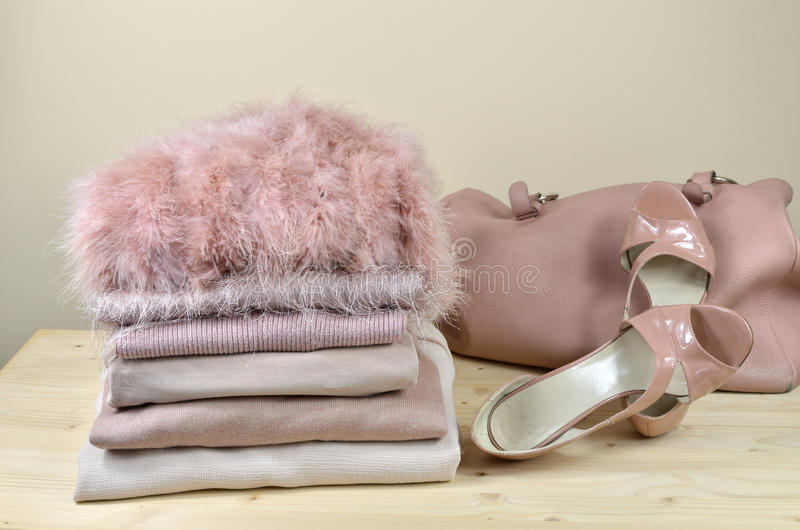 Pink Garments, Sandals and Bag. Pile of different pink garments with elegant pink sandals and a bag beside it - on wooden shelf stock photos