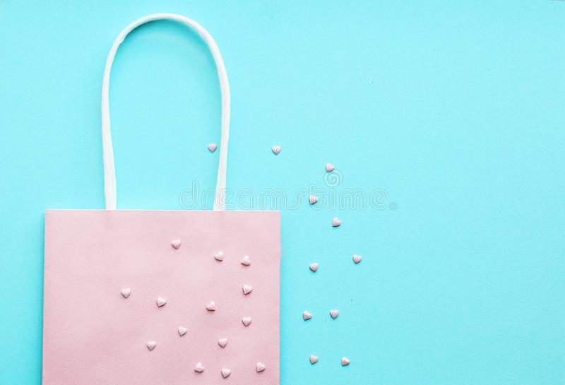 Pink gift bag on a blue background. Gift concept, sale. Pink gift bag on a blue background. Gift concept, clearance sale stock photos