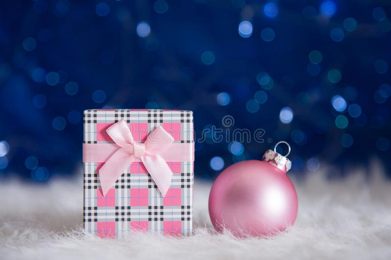 Pink gift box with beautiful Christmas ball on blue bokeh background stock image