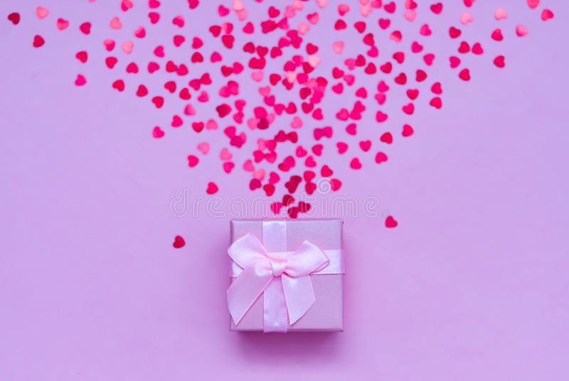 Pink gift box with holographic red hearts on pastel background. Festive backdrop. Top view royalty free stock images