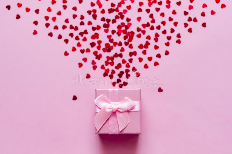 Pink gift box with holographic red hearts on pastel background. Festive backdrop. Top view stock images