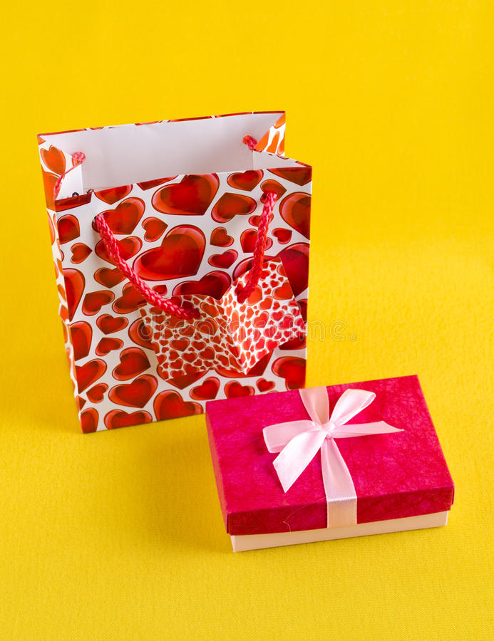 Pink gift box. Gift box and package on a yellow background royalty free stock photos