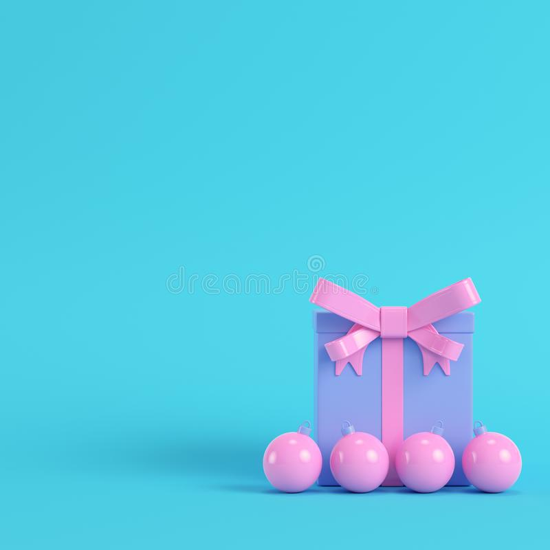 Pink gift box with ribbon bow and christmas ball on bright blue. Background in pastel colors. Minimalism concept. 3d render stock illustration