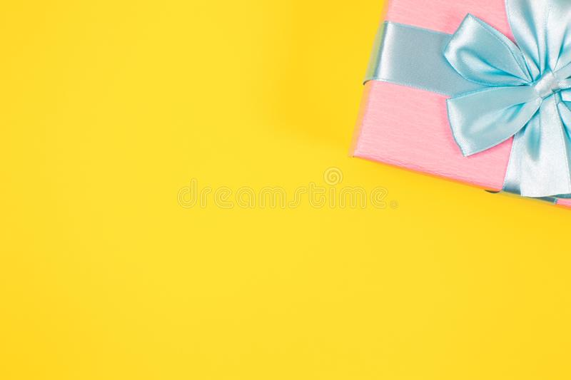 Pink gift box tied with blue ribbon with bow at the top on yellow background. Copy space for text. Minimal flat lay. Top view. stock photo