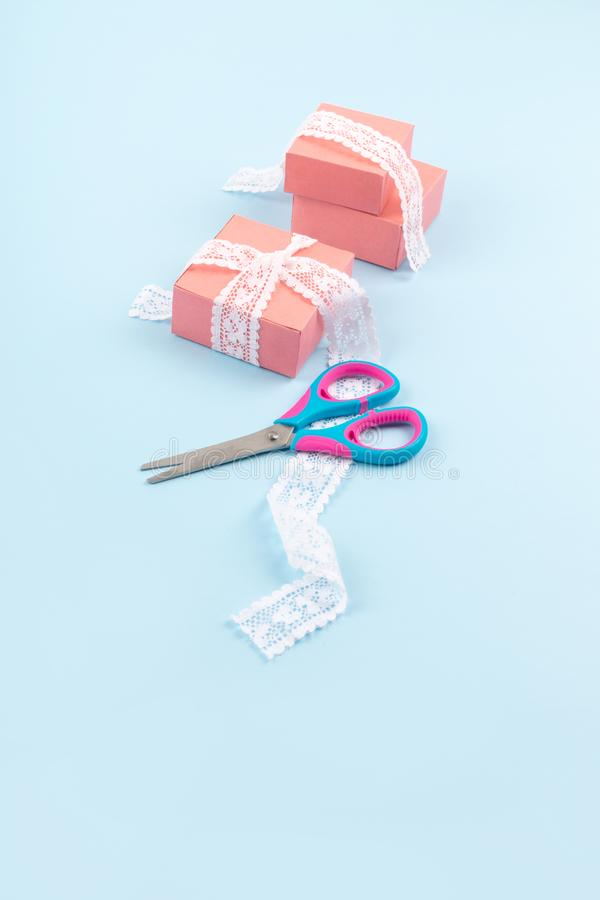 Pink gift boxes with lace and scissors on blue color background. Minimal Gift wrap background stock photos