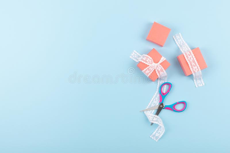 Pink gift boxes with lace and scissors on blue color background. Minimal Gift wrap background stock image