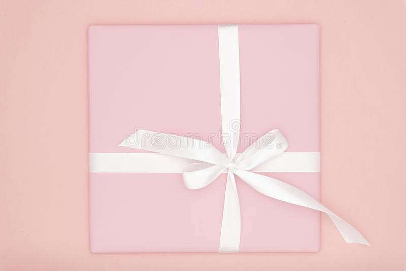 Pink gift or present box flat lay composition for Valentine day or women day, greeting card birthday with on coral background. royalty free stock photography