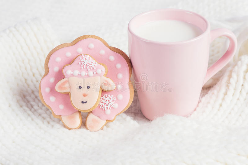Pink gingerbread sheep with cup of milk on white knitted background. Pastel colored stock photo