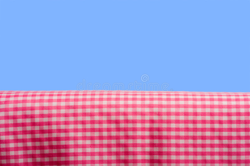 Pink Gingham On Blue Sky. A background consisting of a pink gingham tablecloth on a blue sky background with copy space stock photography