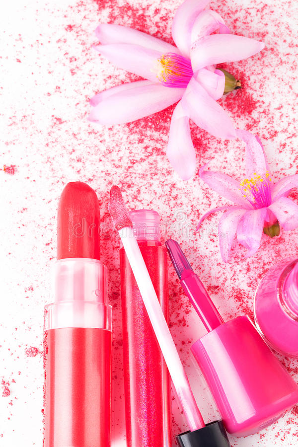 Pink Girly Cosmetcis. Pink Make Up and Cosmetics still life. Girly glamour concept. Pink lipstick, lip gloss and Nail polish, facial powder with flower on white royalty free stock photography