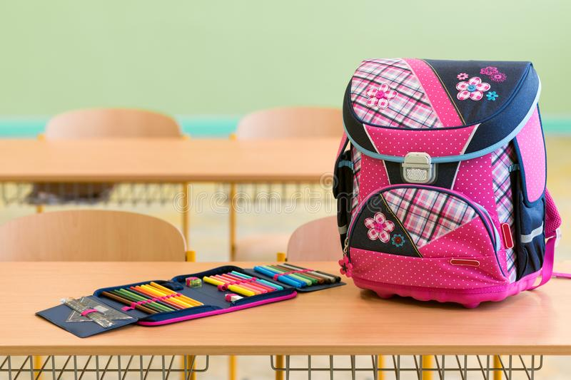 Pink girly school bag and pencil case on a desk in an empty classroom. First day of school. Pink girly school bag and pencil case on a desk in an empty royalty free stock image