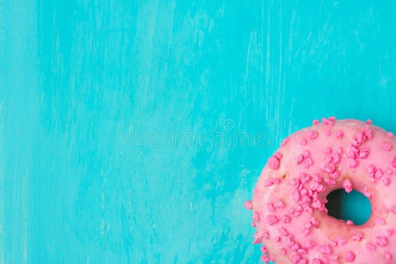 Pink glazed doughnut with sugar sprinkles in bottom corner on light blue background, copyspace, template, birthday stock image