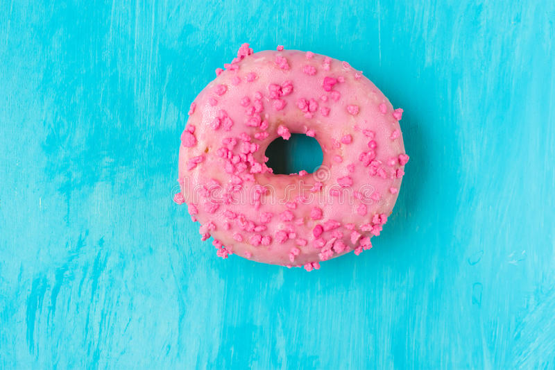 Pink glazed doughnut with sugar sprinkles on light blue background, in the middle, copyspace, template, birthday, card, poste royalty free stock image