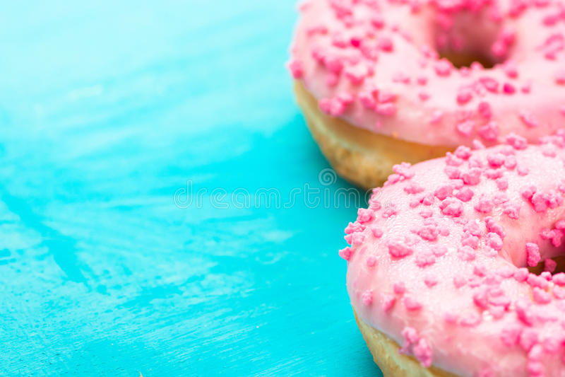 Pink glazed doughnuts with sugar sprinkles on light blue background, copyspace, birthday, card, poster, text ready stock images