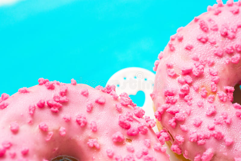 Pink glazed doughnuts with sugar sprinkles on white cake stand with hearts, light blue background, copyspace, birthday, card, post stock images