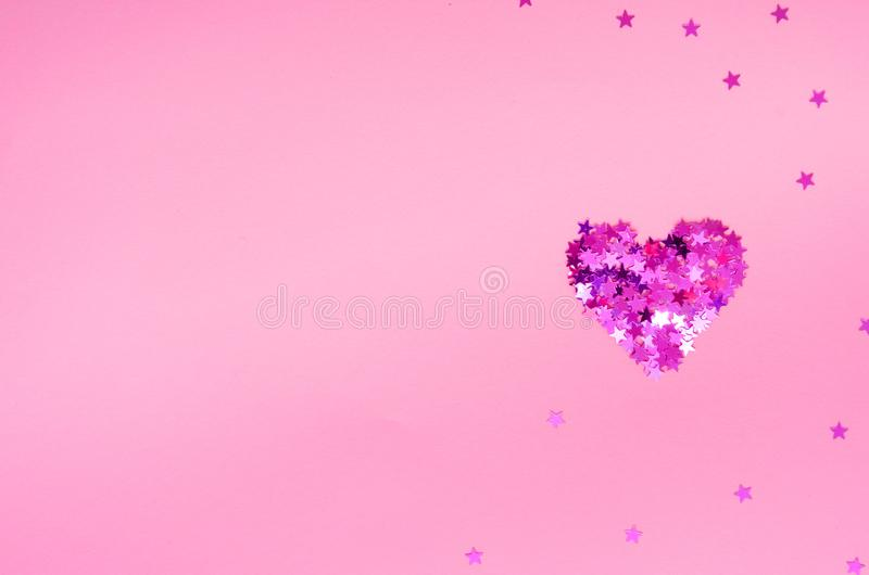 Pink glittering heart made of small stars on a light pink background. Valentines Day card. Flat lay. Copy space royalty free stock images