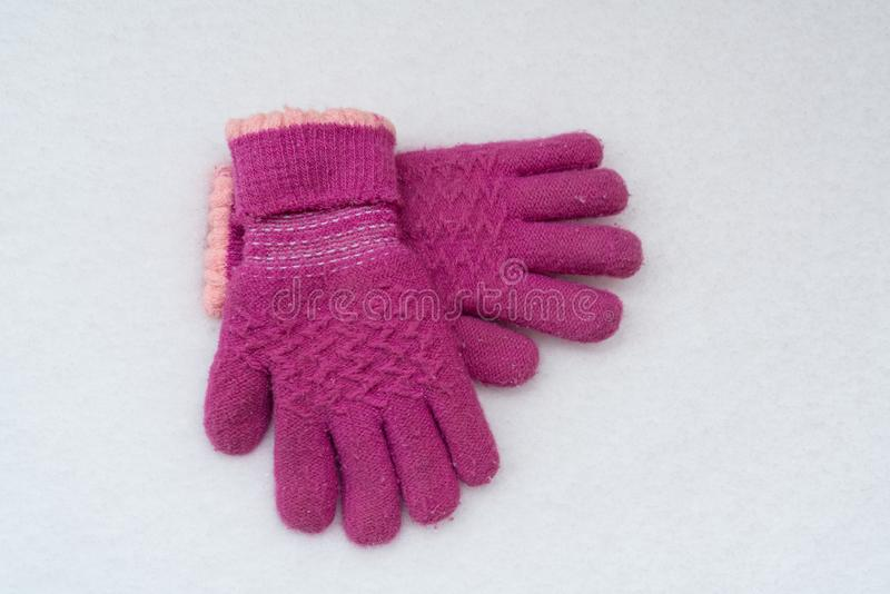 Pink gloves on snow background stock photography
