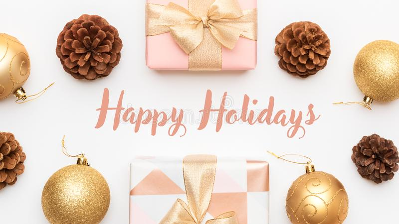 Pink and gold christmas gifts isolated on white background. Wrapped xmas boxes, christmas baubles and pine cones. Christmas composition with copy space royalty free stock photos