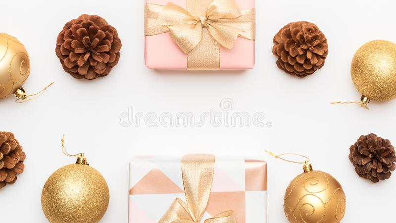 Pink and gold christmas gifts isolated on white background. Wrapped xmas boxes, christmas baubles and pine cones. Christmas composition with copy space stock photo