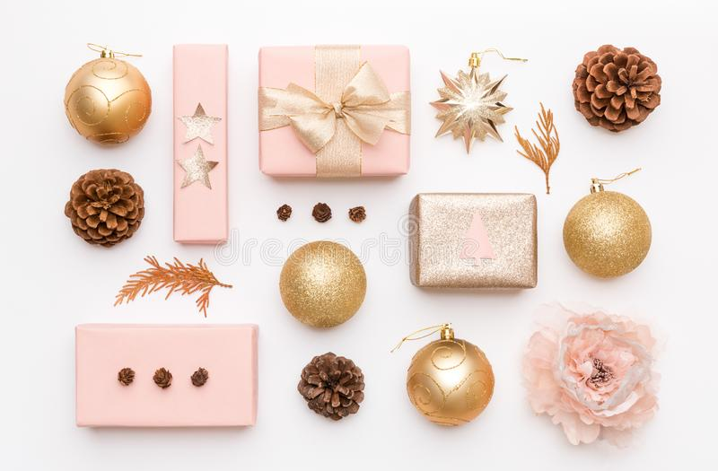 Pink and gold christmas gifts isolated on white background. Wrapped xmas boxes, christmas ornaments, baubles and pine cones. stock images