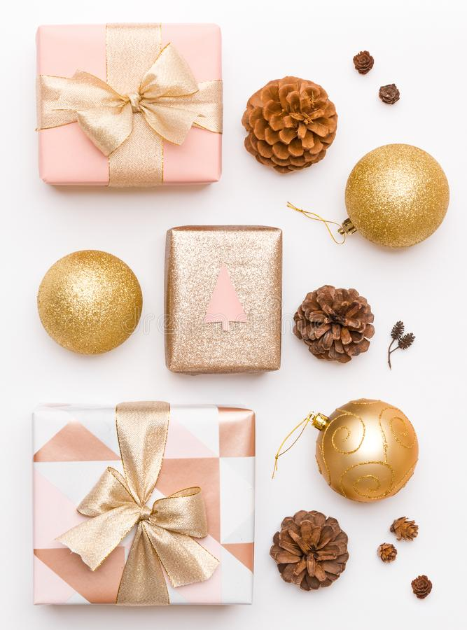 Pink and gold christmas gifts isolated on white background. Wrapped xmas boxes, christmas ornaments, baubles and pine cones. Christmas composition stock photography