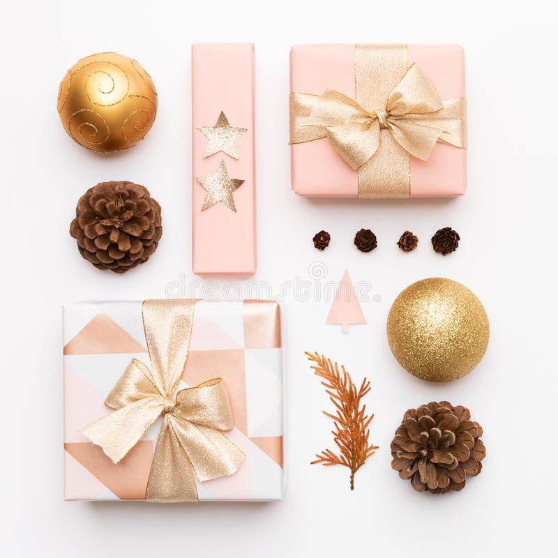 Pink and gold christmas gifts isolated on white background. Wrapped xmas boxes, christmas ornaments, baubles and pine cones. stock photos