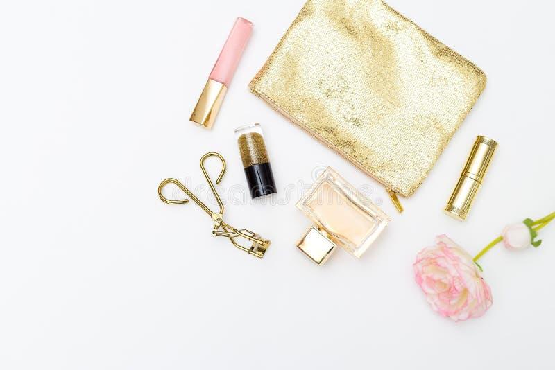 Pink&gold degli accessori e dei cosmetici su un fondo bianco Femin immagini stock