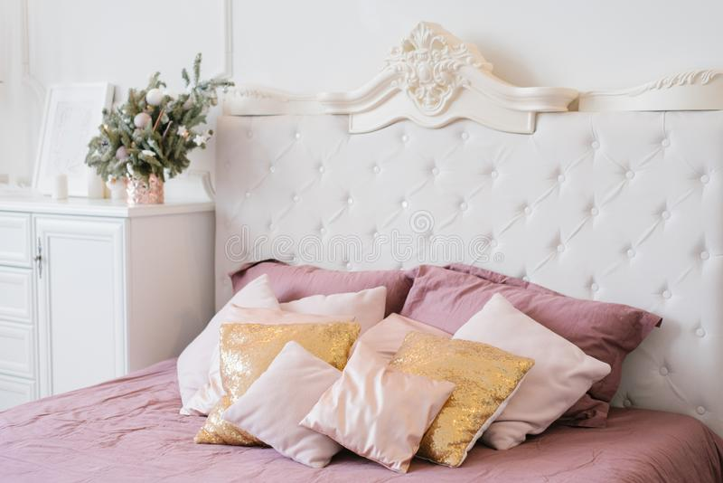 Pink and gold pillows on the large double bed in the bedroom stock images