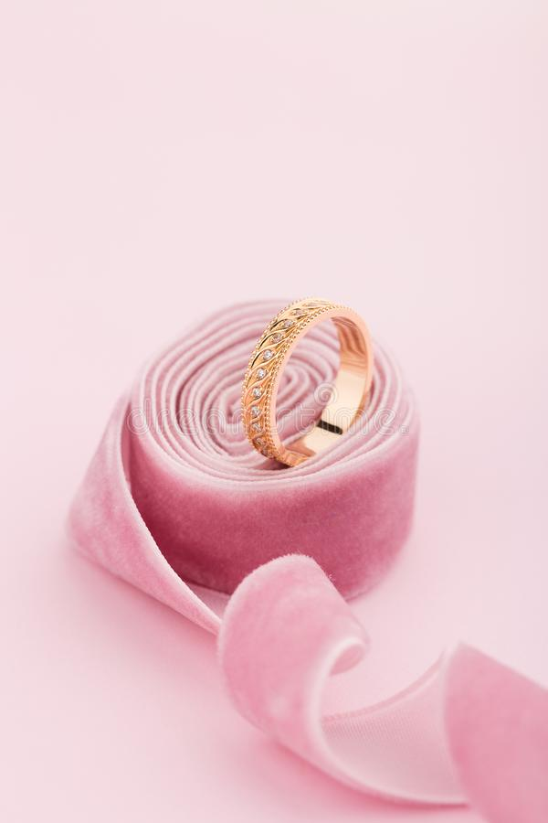 Pink gold wedding ring with diamonds and wave pattern on pink ba. Ckground with ribbon. Product concept for jeweler royalty free stock photo