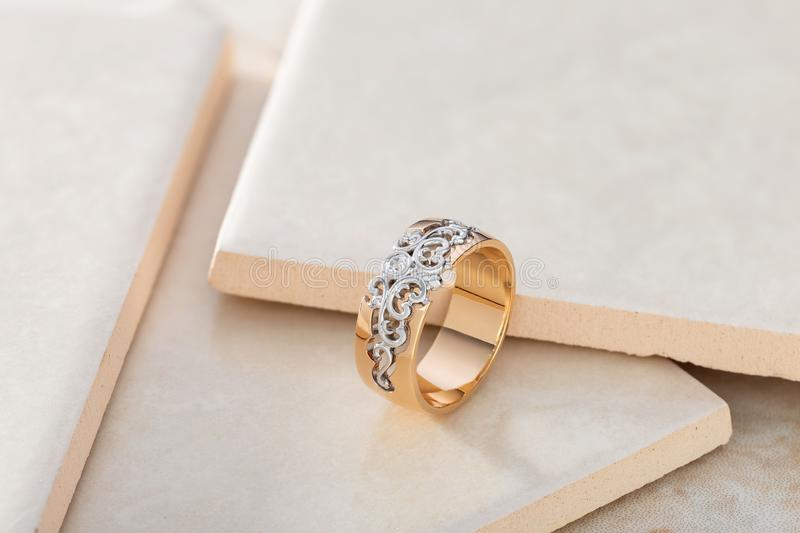 Pink gold and white gold ornament ring with diamond on beige tile background stock image