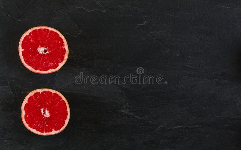 Pink grapefruit cut in half on black slate board photo from above. Wide banner with space for text right.  stock images