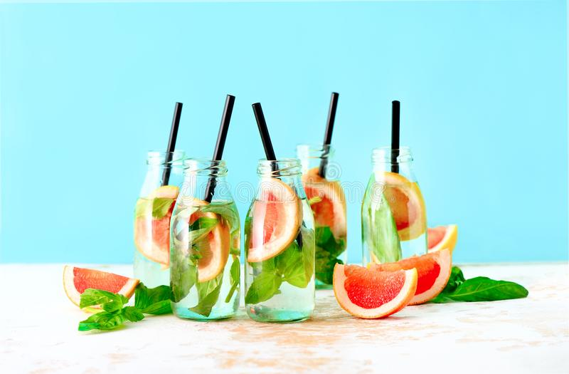 Grapefruit and basil summer refreshing drink. Pink grapefruit and fresh basil infused drink in bottles, spa fruit water, or summer party alcoholic jin tonic royalty free stock photography