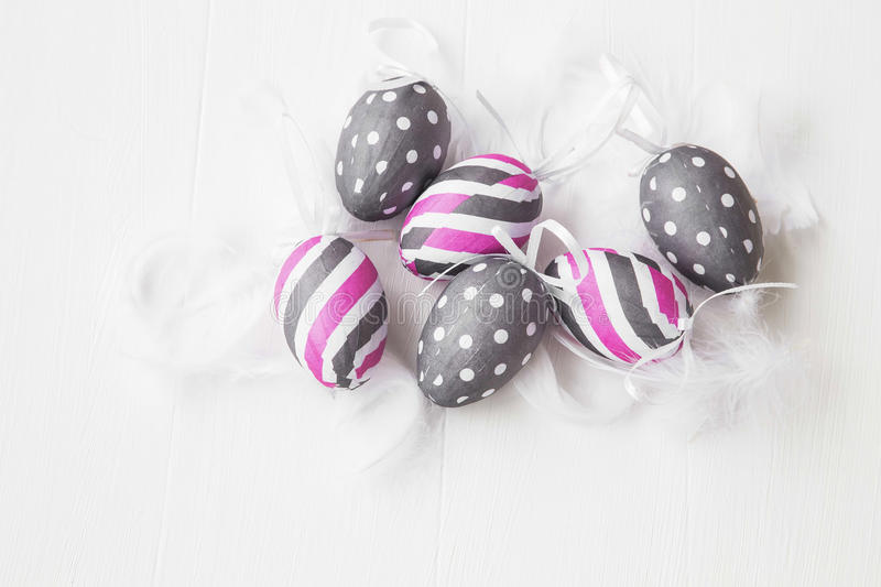 Pink and gray Easter eggs decorated with feathers on white background royalty free stock image