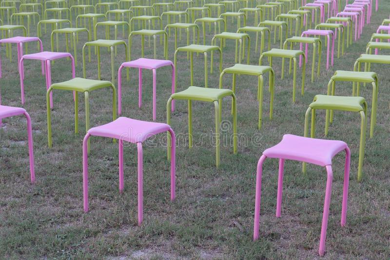 Pink and green chairs arranged in rows on the lawn royalty free stock image