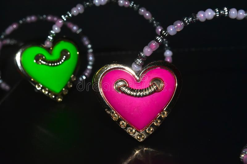 Pink & green coloured heart shaped isolated showpiece object. The beautiful pink & green coloured heart shape plastic object with unique dark background stock stock photo