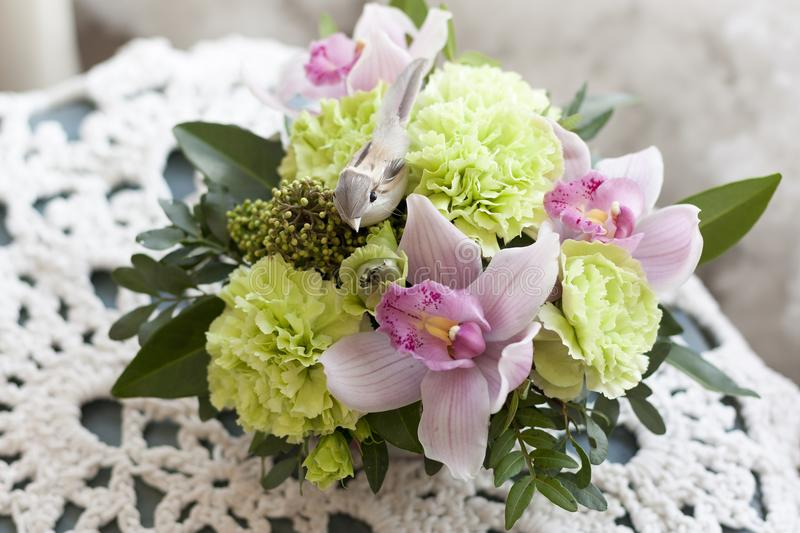 Pink-green floral arrangement with decorative bird stands on a lace white napkin. On the table royalty free stock photos