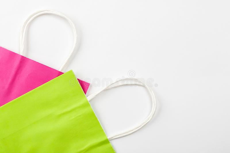 Pink and green paper bags with handles on a white background top view, copyspace.  royalty free stock photos