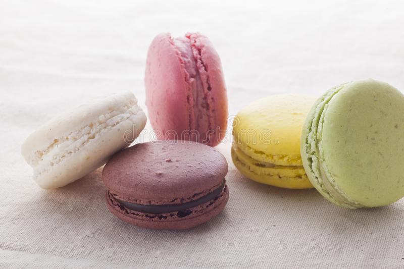 Multi-colored macaroons put on a white fabric royalty free stock photography