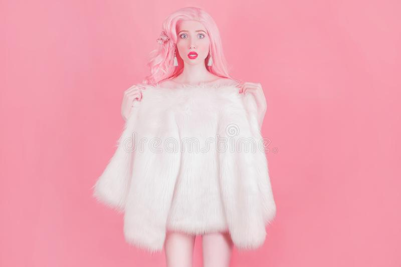 Pink hair woman in fur coat on pastel background. Beautiful girl in long wavy wig. Minimal spring trend with wow effect. Summer stock photos