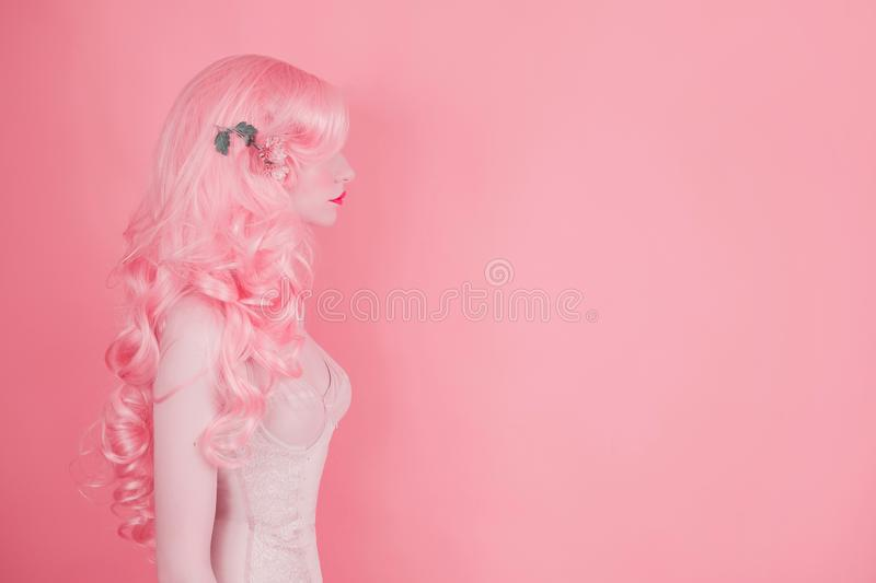 Pink hair woman in wig on pastel background. Beautiful sexy girl in long wavy wig. Minimal spring trend. Pastel color design. 2019 royalty free stock photos
