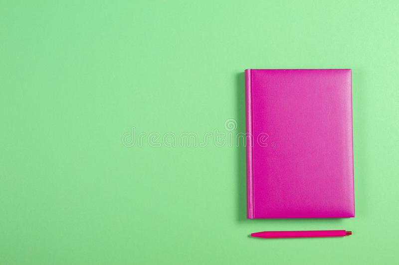 Pink hardcover book and pen on green background stock photo