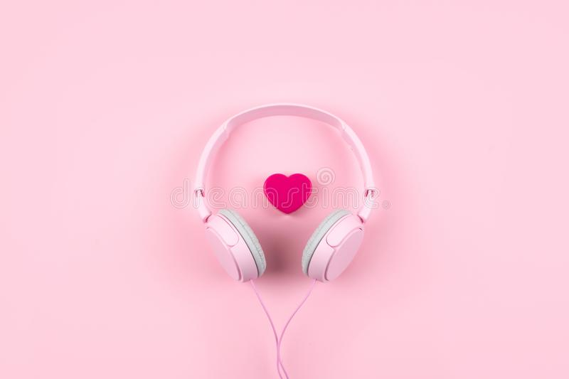 Pink headphones and heart on pink background. Minimal Music concept. Top view. Flat lay. Pop beat dj summer sound fashion radio bright stereo audio colorful royalty free stock image
